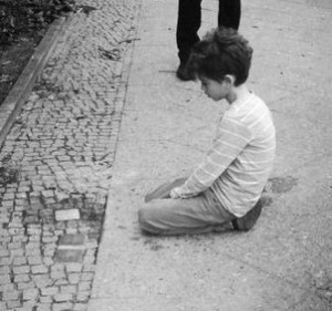 "Gunter Demnig, the creator of the Stolpersteine project twitted this photo of a child viewing a stumbling stone. The project is called the ""world's largest decentralized memorial"""